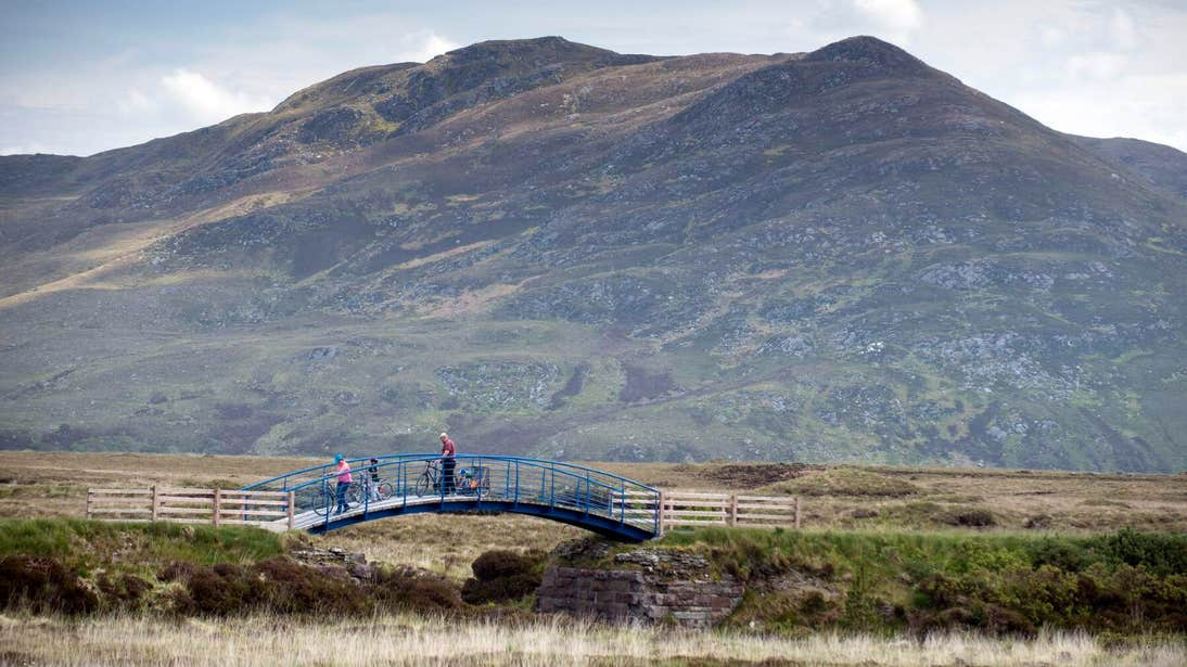 Family crossing a bridge on bikes on The Great Western Greenway in Mayo
