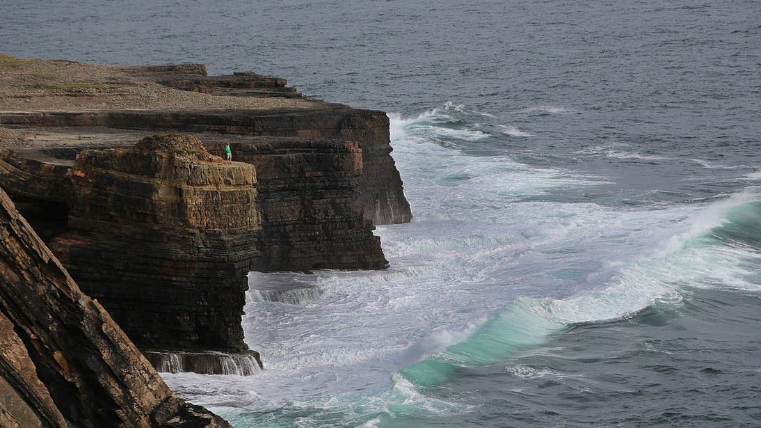 Person standing on a cliff at Loop Head in Clare