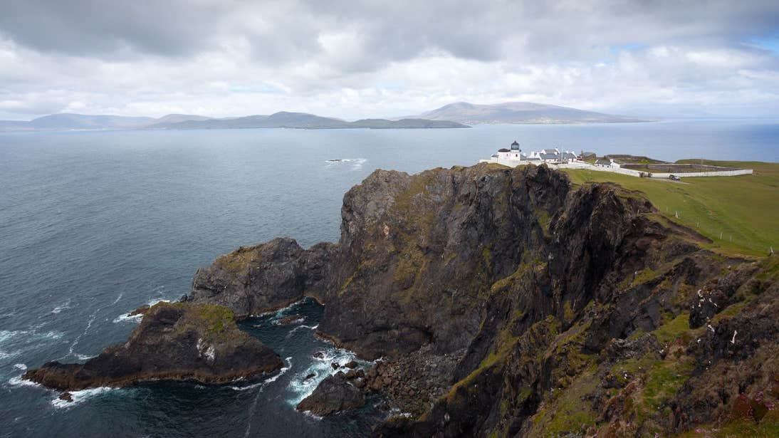 A view of a lighthouse on a cliff and waves crashing against the rocks below at Clare Island Lighthouse, Mayo