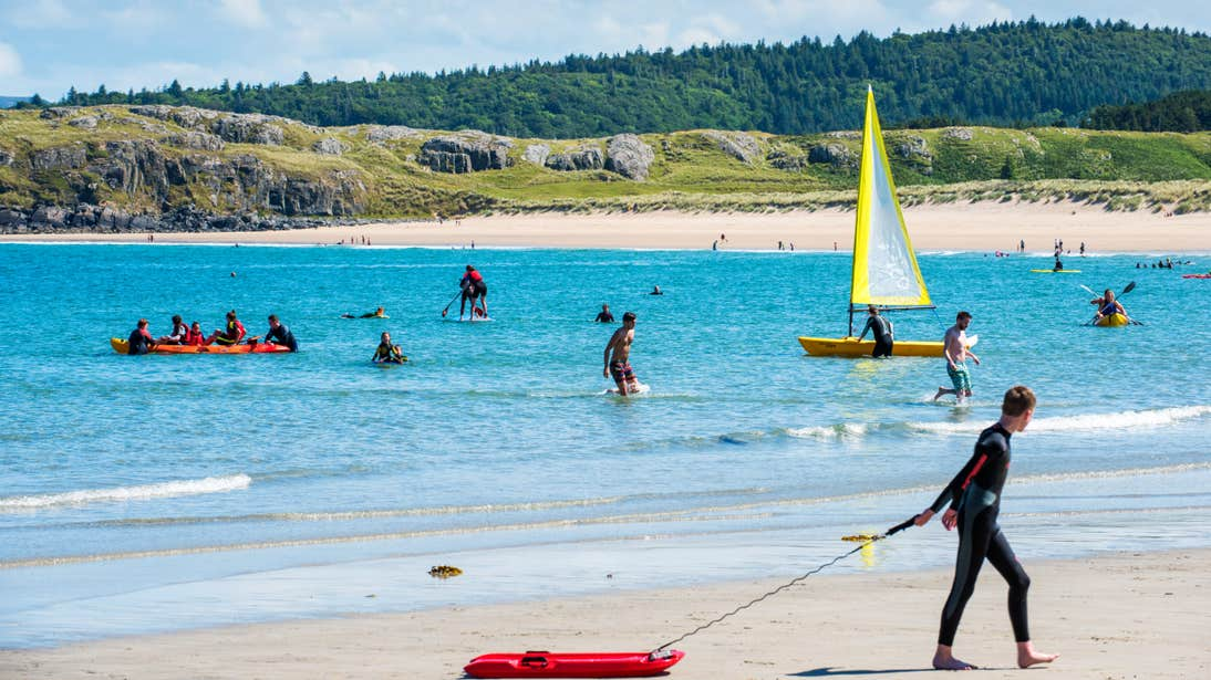 Man pulling a red board along the sand in front of people playing in the sea at Marble Hill Beach, Donegal