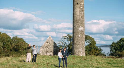 People exploring ancient stone monuments at Holy Island in County Clare.