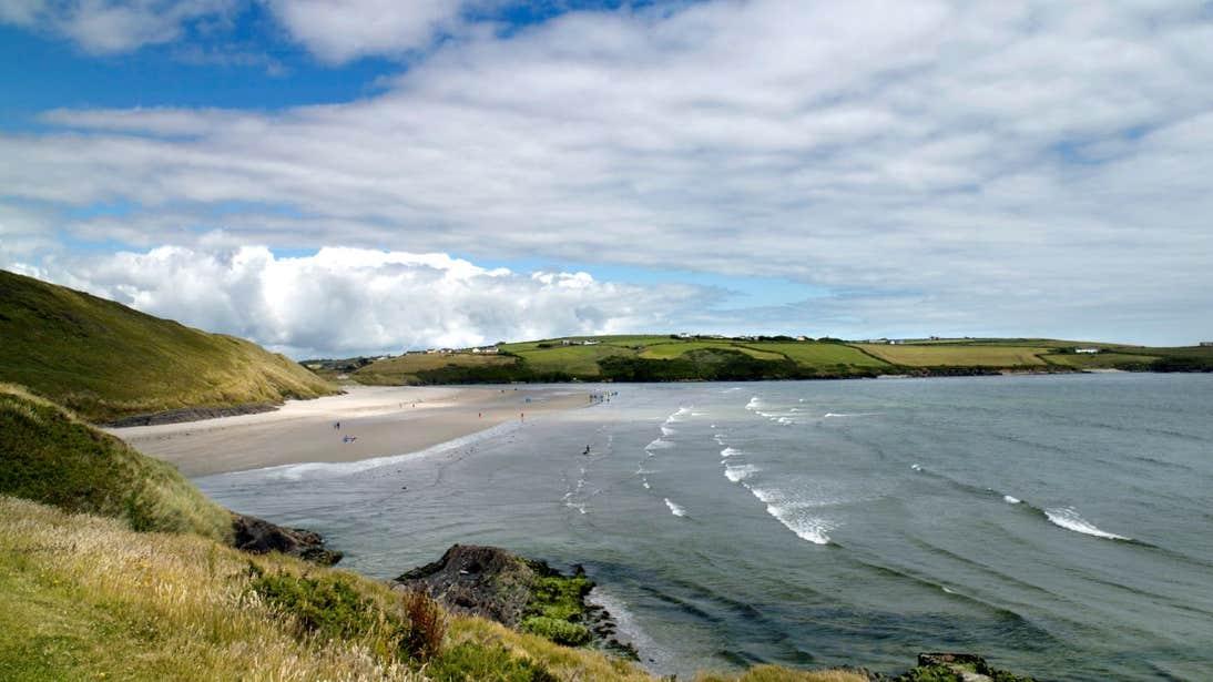 Waves on Inchydoney Beach in West Cork under green hills