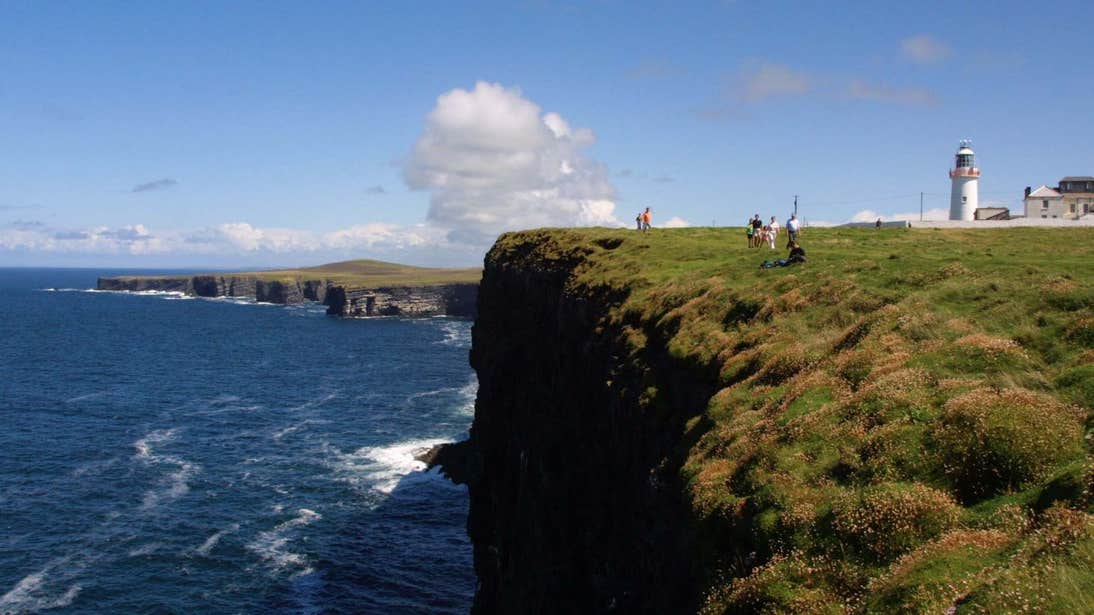 People walking on a trail beside a cliff with a lighthouse in the distance at Loop Head, Clare