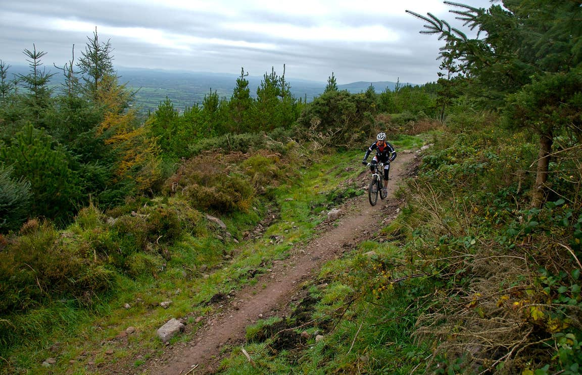 A man wearing a helmet and cycling gear navigating one of the Ballyhoura Mountain Bike Trails