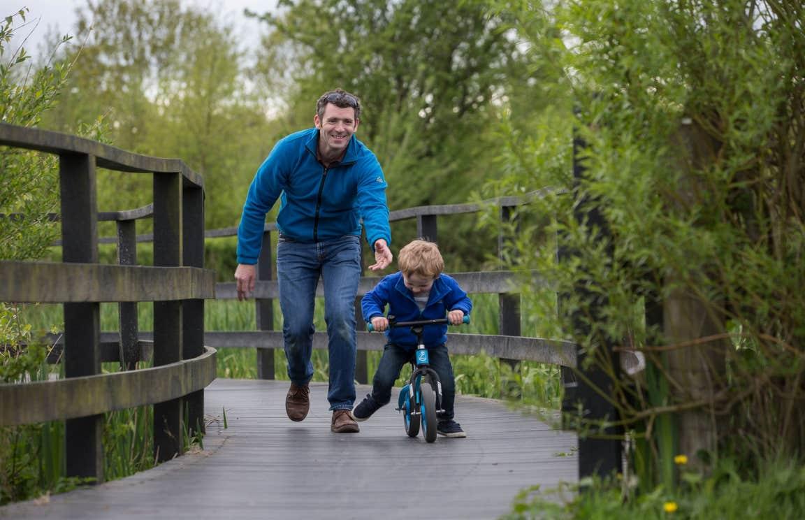A man guiding a little boy cycling on a bike at Dún na Sí Amenity and Heritage Park, Westmeath