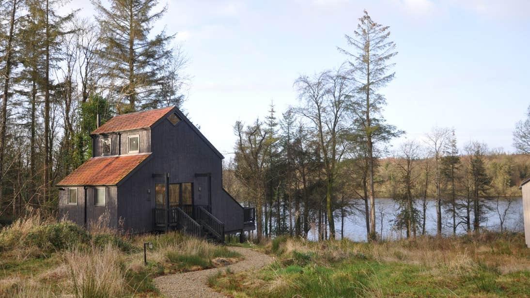 A wooden cabin beside a calm lake in Cavan