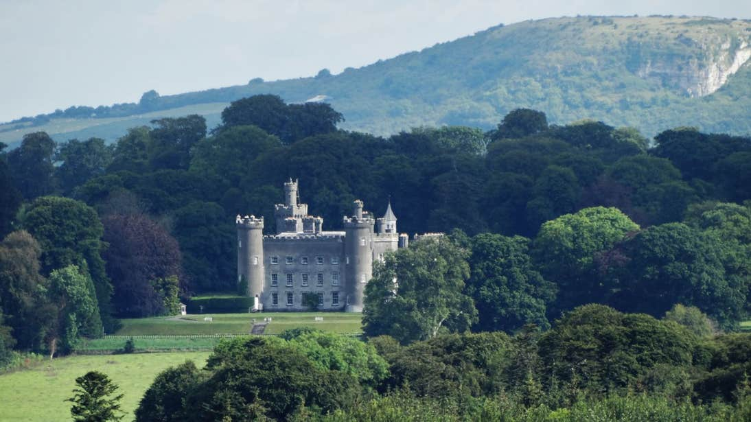 Tullynally Castle surrounded by trees and green hills in County Westmeath