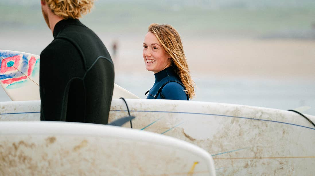 Two surfers in wetsuits carrying their surfboards in Lahinch, County Clare
