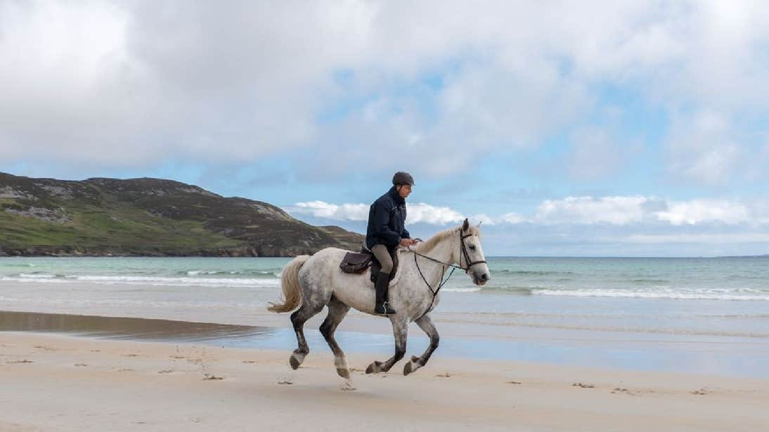 Person horse riding on the beach in County Donegal