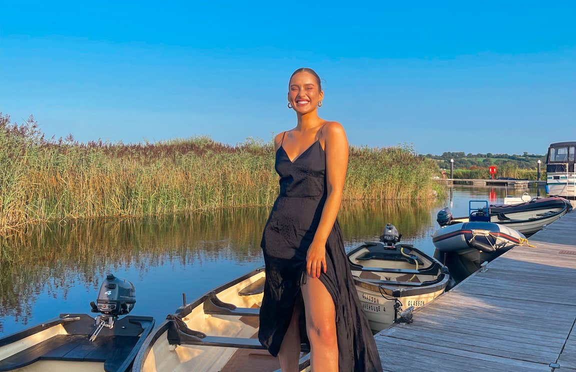 Roz Purcell wearing a black dress standing on a deck in front of a row of boats at Glasson Lakehouse, Westmeath
