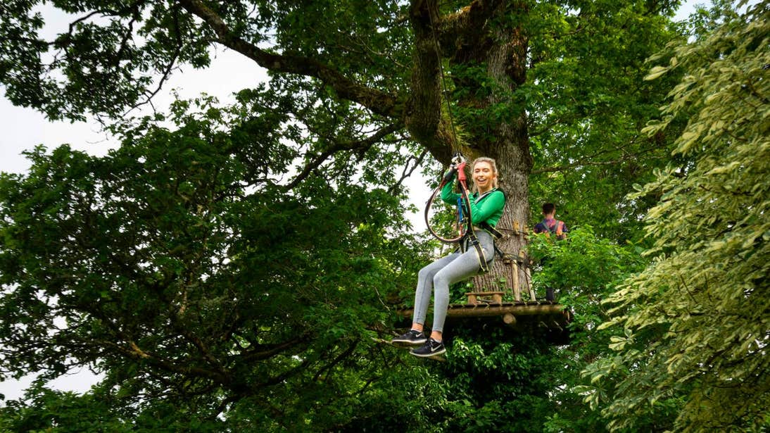 Girl on a zipline in a forest at Lough Key Forest Park and Adventure Centre, Co. Roscommon
