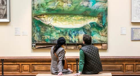 Two people enjoying a painting in Crawford Art Gallery in County Cork