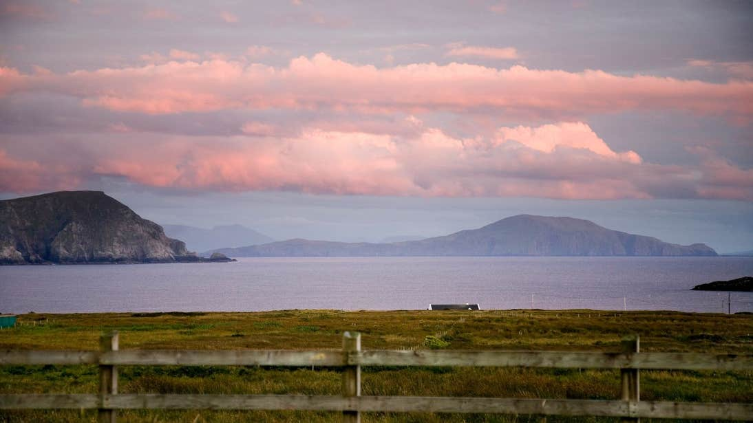 Looking out at a sunset across a field towards the ocean in Mayo on Achill Island