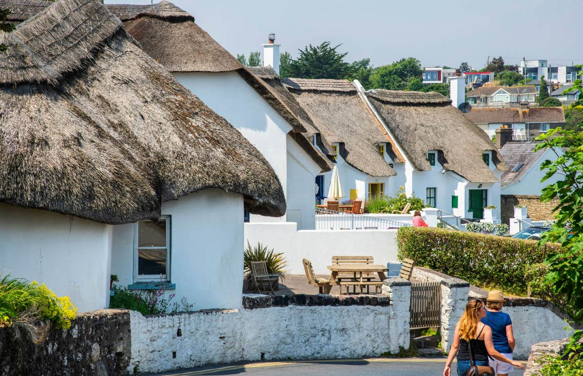 People walking by white thatched cottages in Dunmore East, Co Waterford