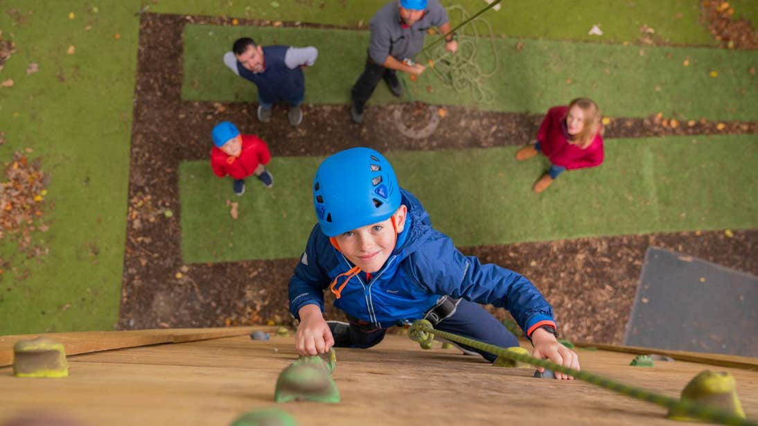 Young boy smiling at the camera while on a wooden climbing wall with people watching from below.