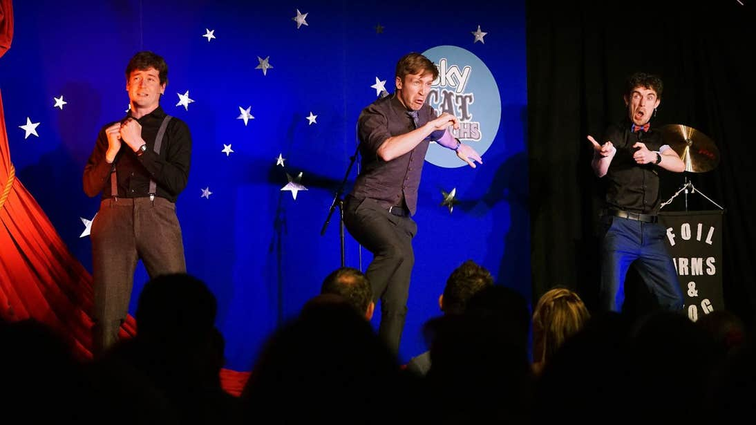 Three men performing on stage in front of a packed audience at the Cat Laughs Festival