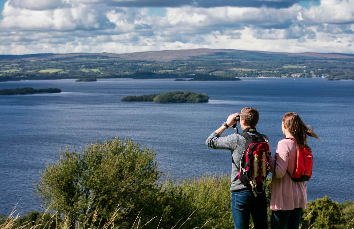 A couple using binoculars to look out over Lough Derg, County Tipperary