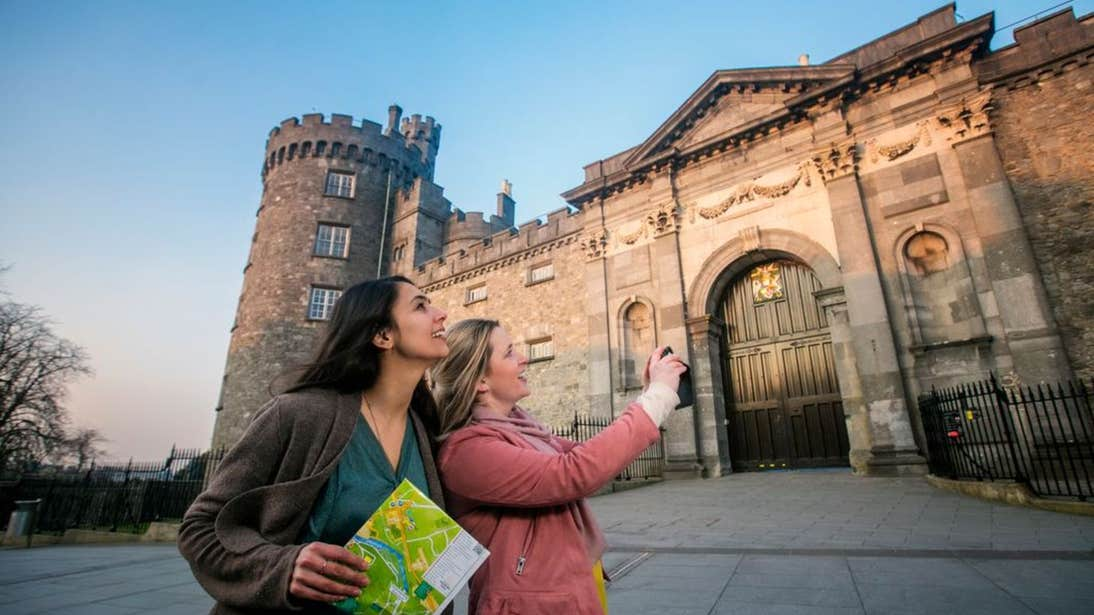 Two women taking pictures outside Kilkenny Castle, County Kilkenny