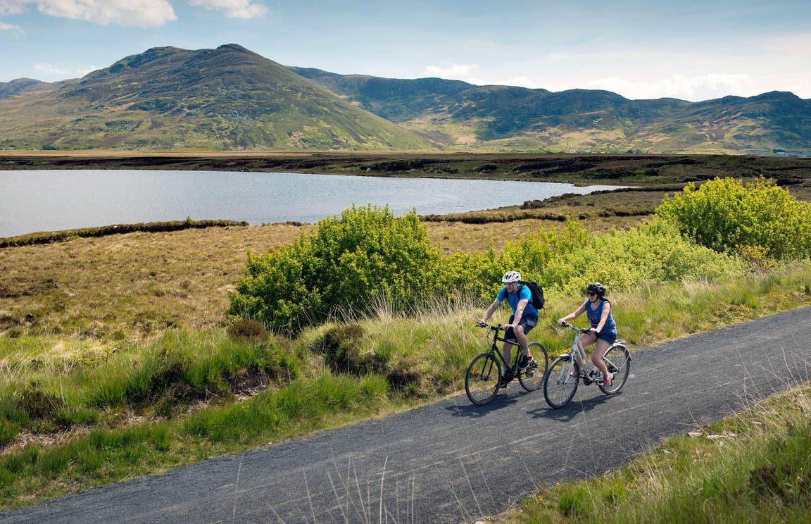 Two people cycling on The Great Western Greenway beside the sea in Mayo