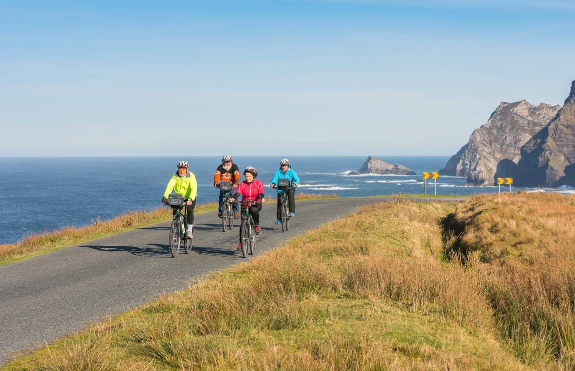 Family cycling along the coast in Donegal