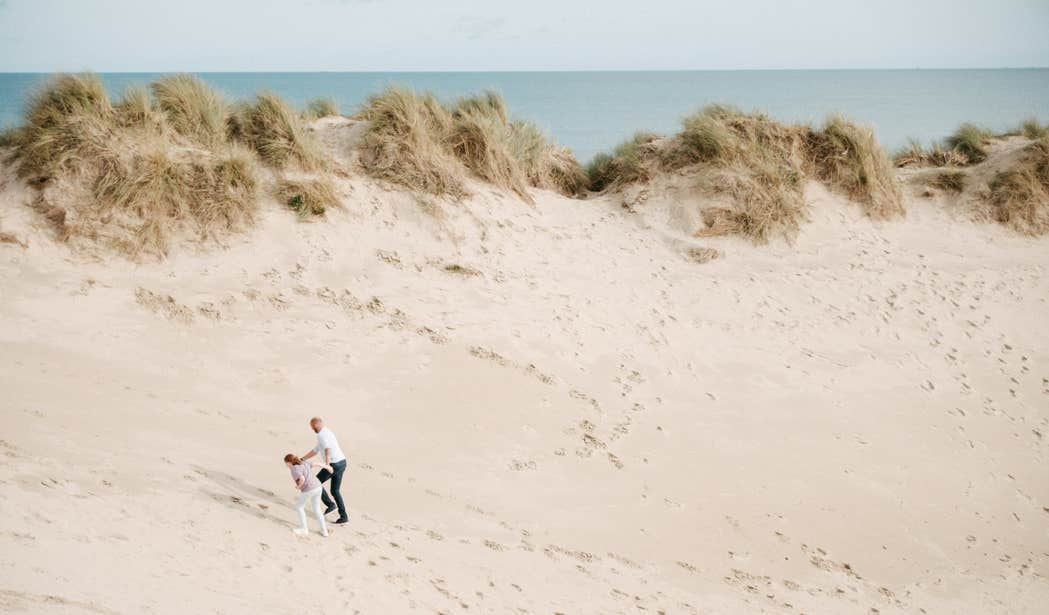 Two people walking up the sand dunes at Curracloe Beach in Wexford.
