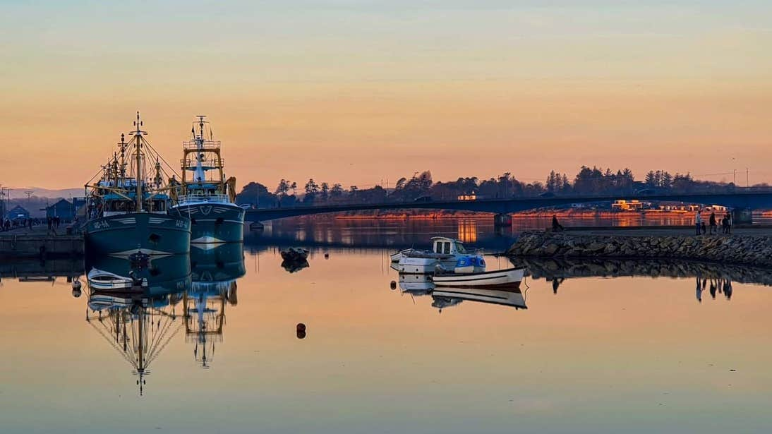 Four boats on still water at Wexford Harbour, County Wexford at sunset.