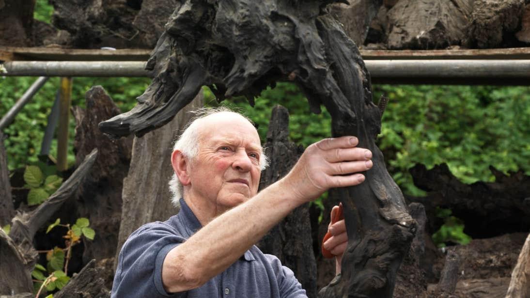 Man creating a piece of art at Bog Oak Sculpture, Longford