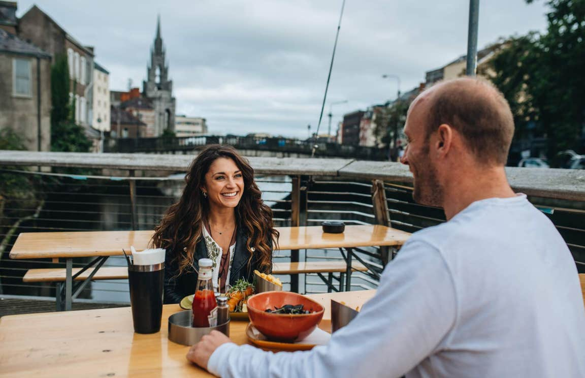 Couple dining by the River Lee in Cork City.