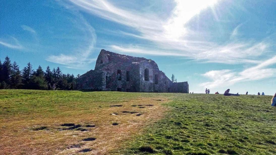 People sitting on grass and walking around the Hellfire Club in Dublin