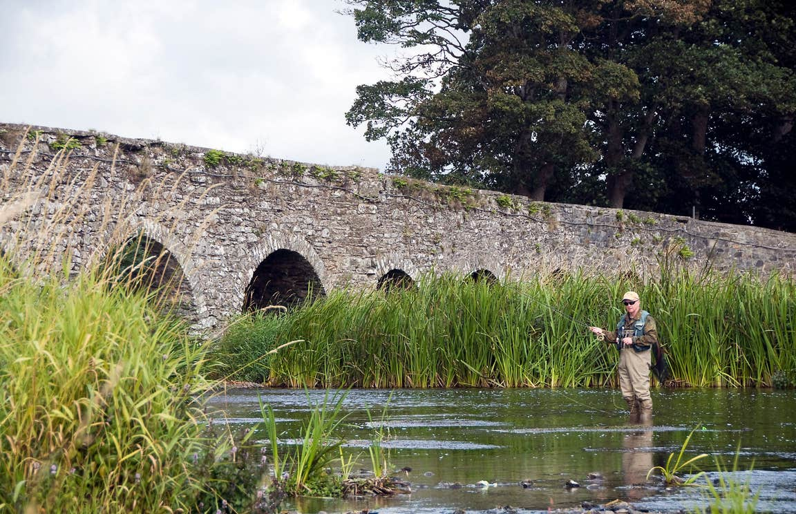 A man standing in water fishing beside an arched bridge