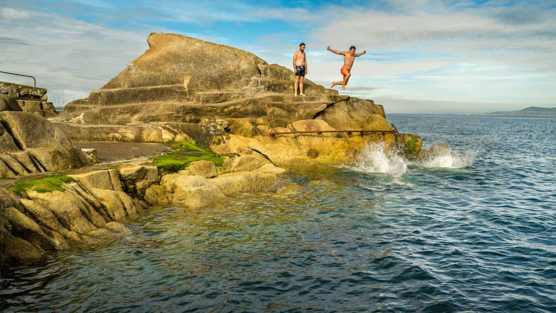 People jumping off rocks at The Forty Foot in Sandycove, Dublin