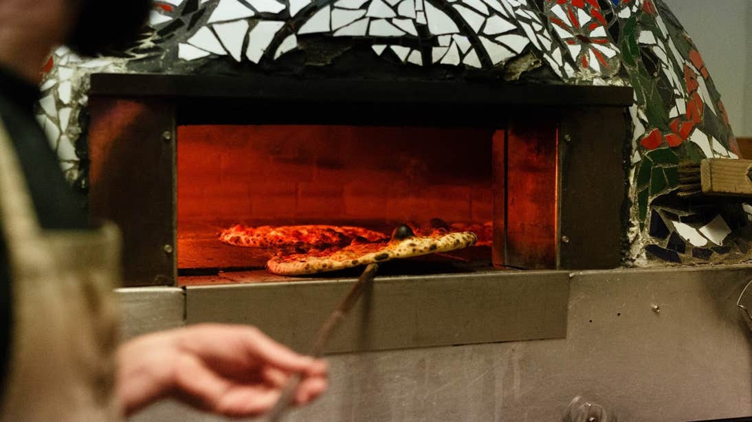 Man taking out a pizza from a pizza oven in Franciscan Well Brewery in Cork City.