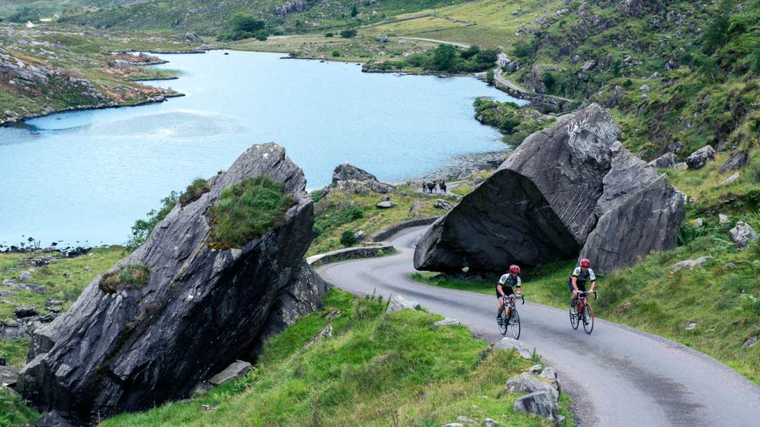 Two people cycling up a hill on the Ring of Kerry in County Kerry