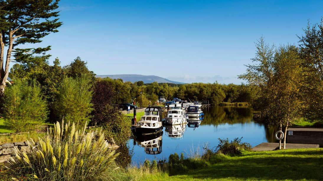 Boats on the River Shannon on a clear day with a mountain in the background