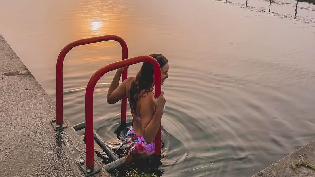 Roz Purcell standing in the water at sunrise in Banagher Outdoor Swimming Pool, Offaly