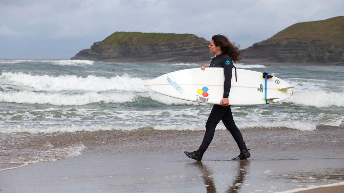 A woman wearing a wetsuit and heading towards the waves at Bundoran