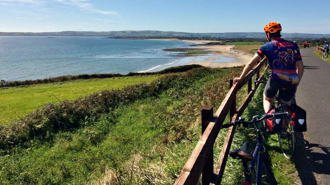 A cyclist admiring the incredible coastal views on the Waterford Greenway