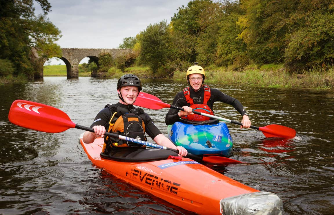 Two people in orange boats kayaking down a river.