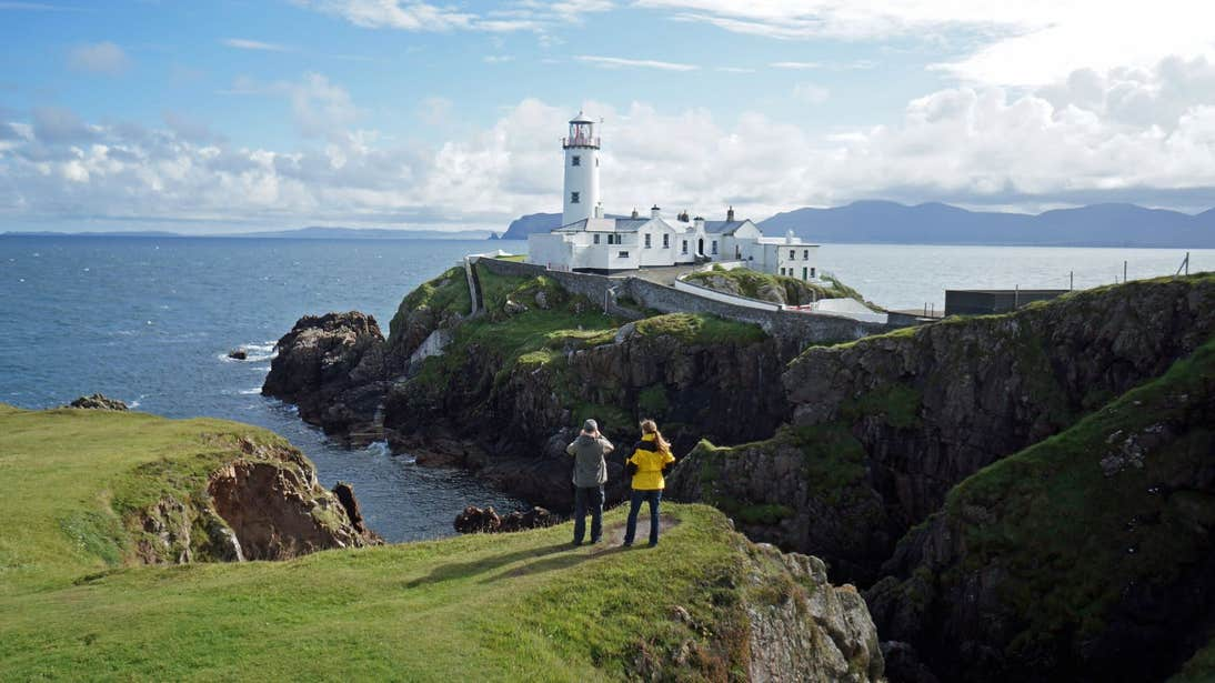 Two people taking photos of Fanad Head Lighthouse