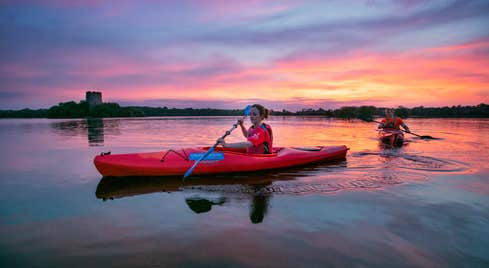 Two people kayaking on Lough Oughter in County Cavan and watching the sunset