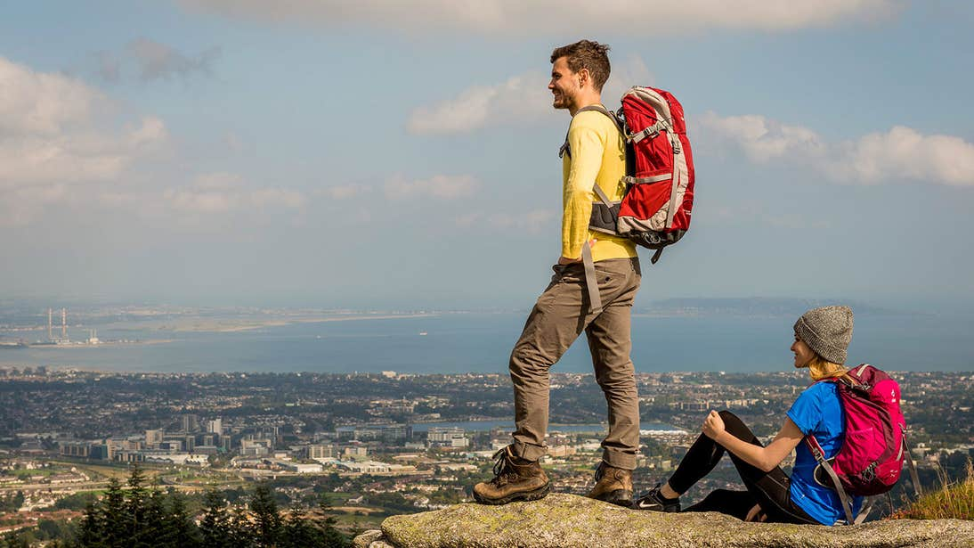 Two people standing on rocks admiring the views from Three Rock Mountain, County Dublin