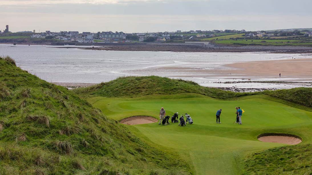 Golfers playing a round by the ocean in Lahinch County Clare