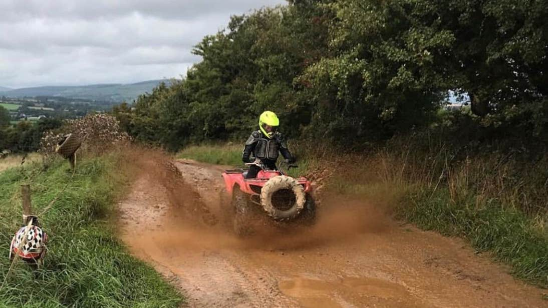 A person riding a quad through a muddy puddle with Quadventure, County Wexford
