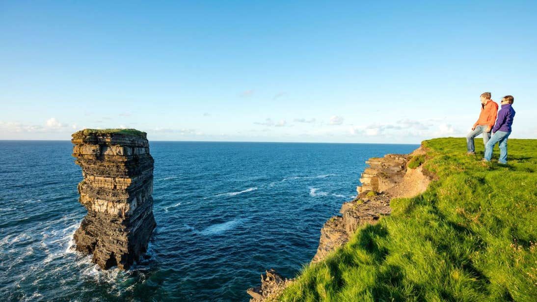 Two people admiring the views of the sea stack at Downpatrick Head