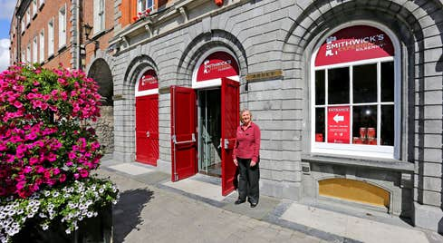 A female staff member standing outside the Smithwicks Kilkenny Experience building
