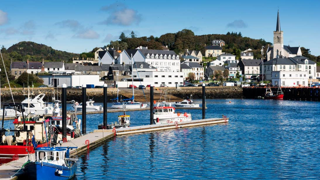 Boats in Killybegs Harbour, Co. Donegal in front of buildings and a church