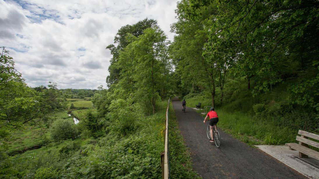 Two people cycling along a path on the Limerick Greenway, Limerick