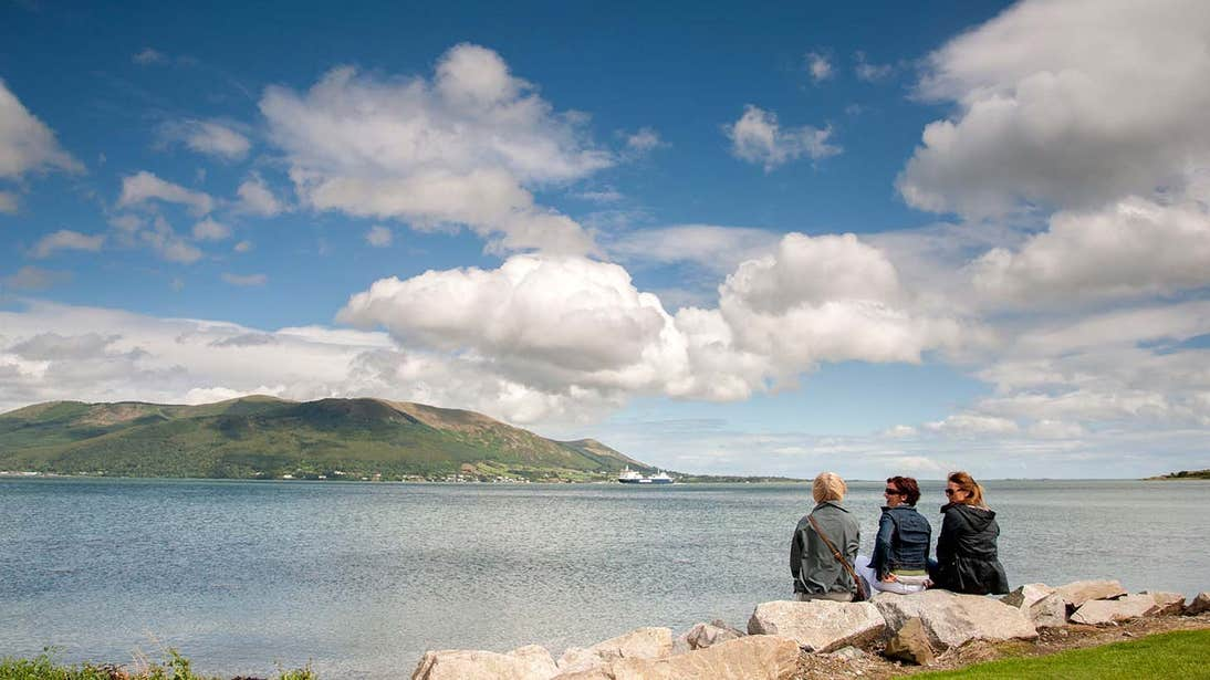 Three people looking at a mountain on the far side of a lake in Carlingford County Louth