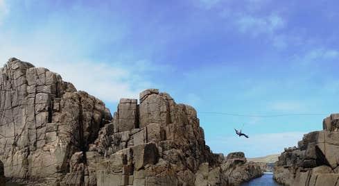 Zip lining between rocks over the sea