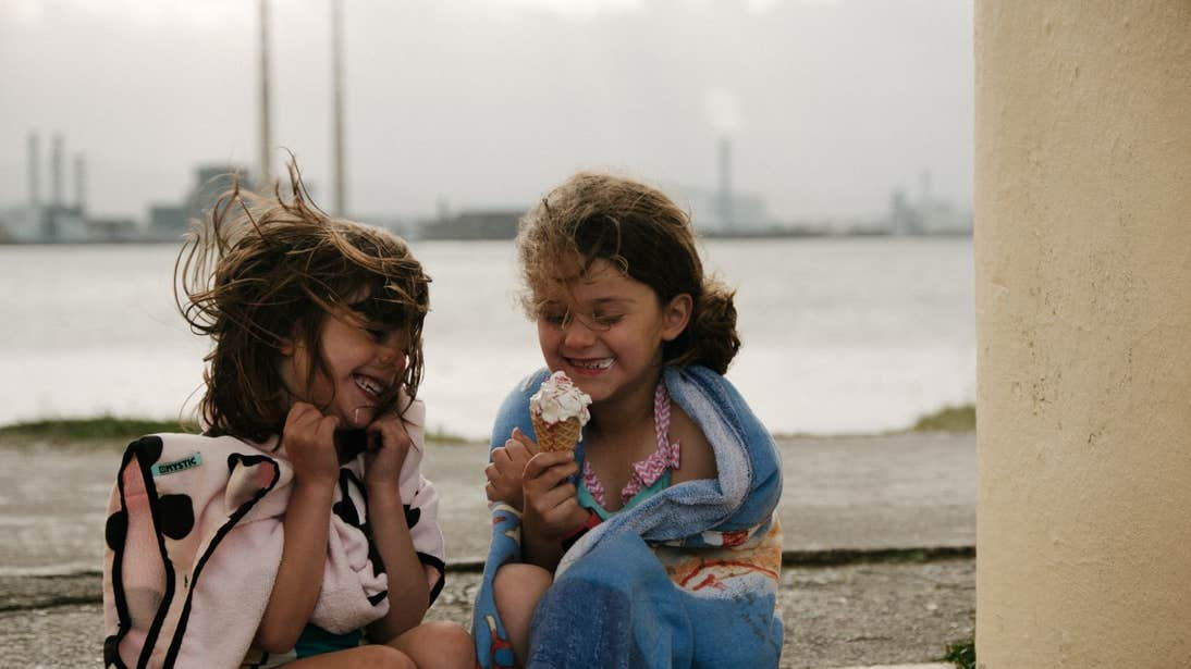 Two young girls enjoying ice cream by the sea in Dublin.
